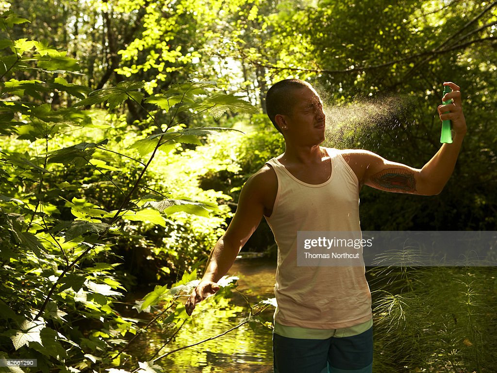 Young man spraying bug spray : Stock Photo