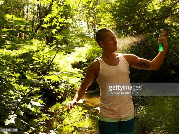 Young man spraying bug spray