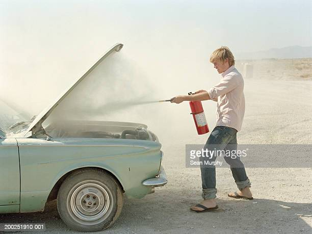 Young man spraying fire extinguisher in car hood