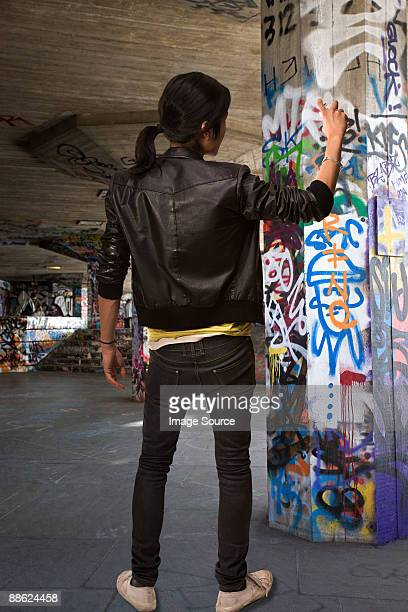 A young man spraying graffiti