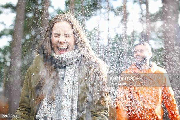 Young man sprinkling girlfriend with water in forest
