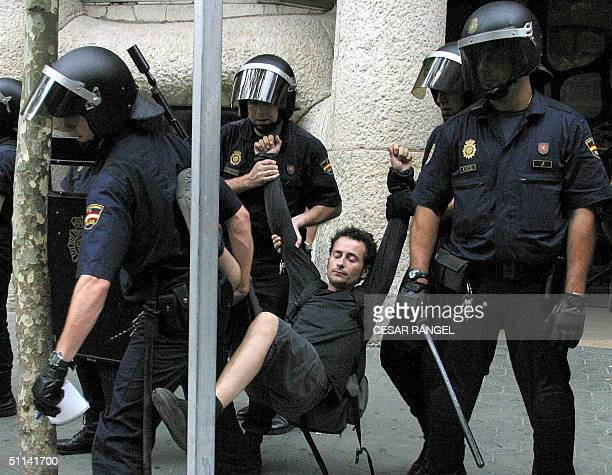 A young man squatter is removed 04 August 2004 by police from Barcelona's La Pedrera building created by Antoni Gaudi for protesting against the...