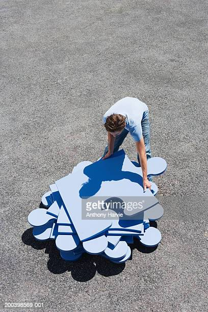 Young man stacking large blue jigsaw pieces