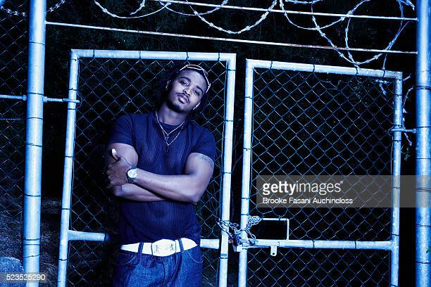 Young man standing against chain-link fence at night