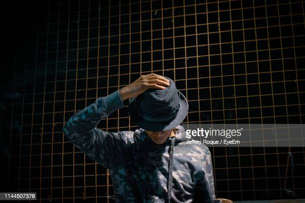 young man standing against metal grate - jeffrey roque stock photos and pictures