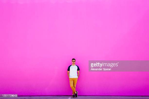 young man standing against pink wall - magenta stock pictures, royalty-free photos & images