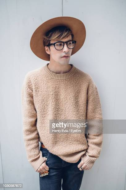 young man standing against wall - pull photos et images de collection