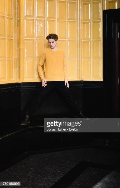 young man standing against wall - disguise stock pictures, royalty-free photos & images