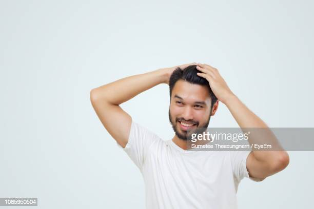 young man standing against white background - 髪に手をやる ストックフォトと画像