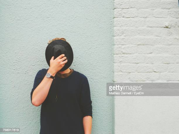 Young Man Standing Against White Wall