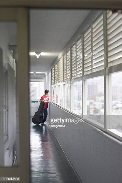 young man standing aisle - guitar case stock pictures, royalty-free photos & images