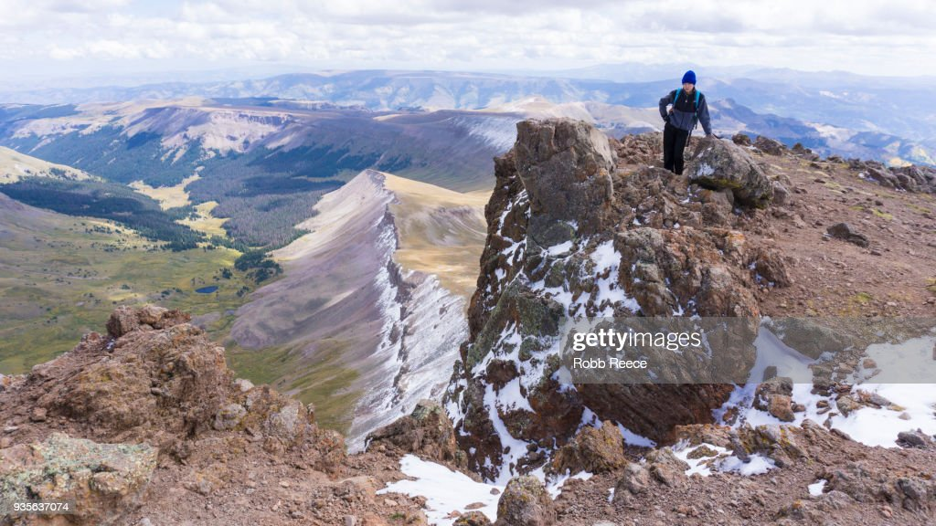 A young man standing alone on a remote mountain peak : Stock Photo