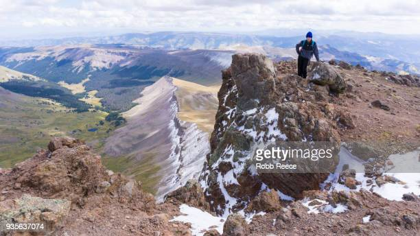 a young man standing alone on a remote mountain peak - robb reece stockfoto's en -beelden