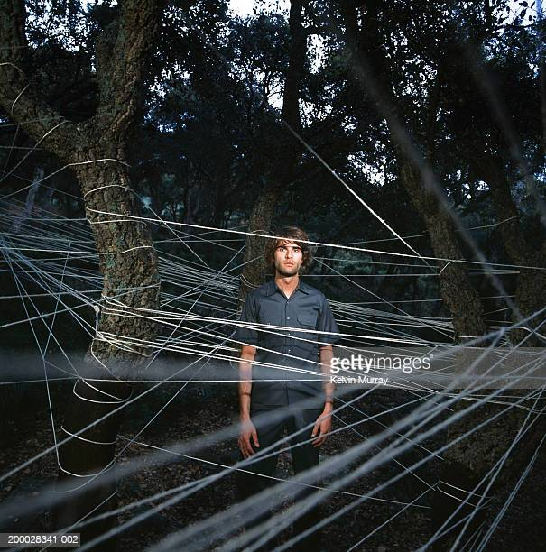 Young man standing amongst trees entwined with string, portrait