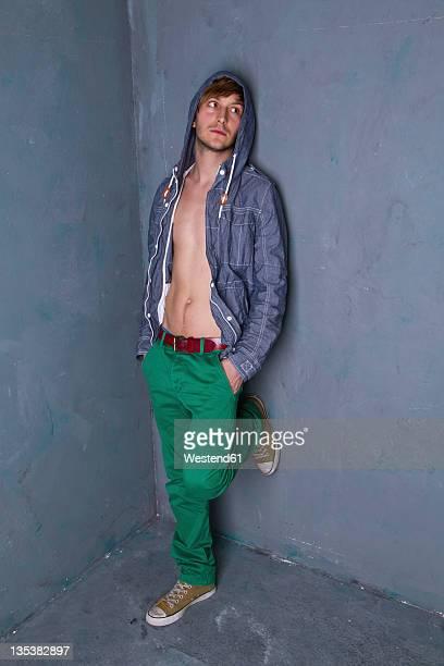 young man standing and leaning agaist dirty wall - helemaal losgeknoopt stockfoto's en -beelden