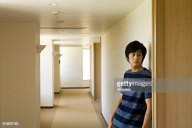 Young man standing and waiting in corridor