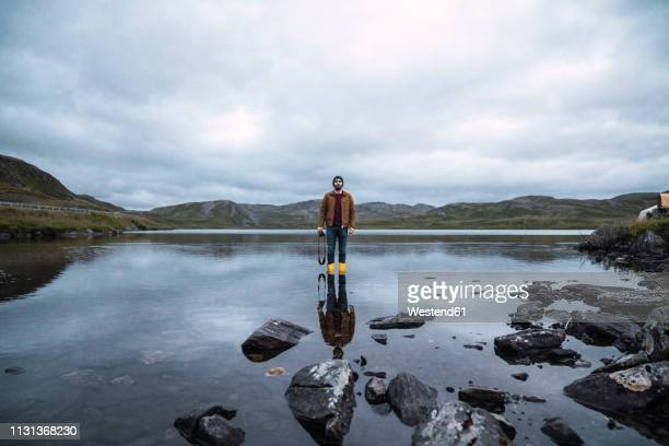 young man standing ankle deep in water, holding camera - wading stock pictures, royalty-free photos & images