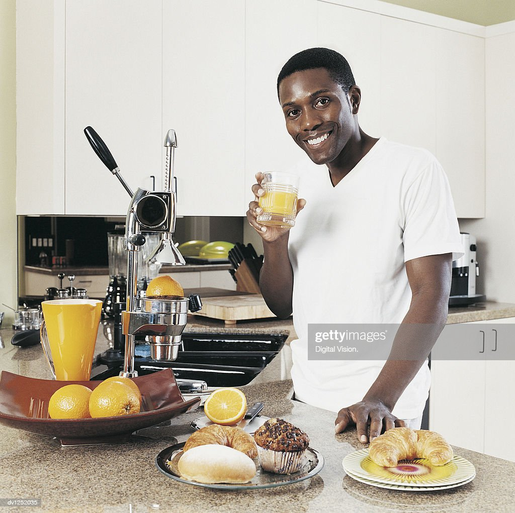 Young Man Standing at a Kitchen Counter Holding a Glass of Orange Juice : Stock Photo