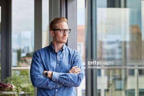 young man standing at balcony door thinking - デニムシャツ ストックフォトと画像
