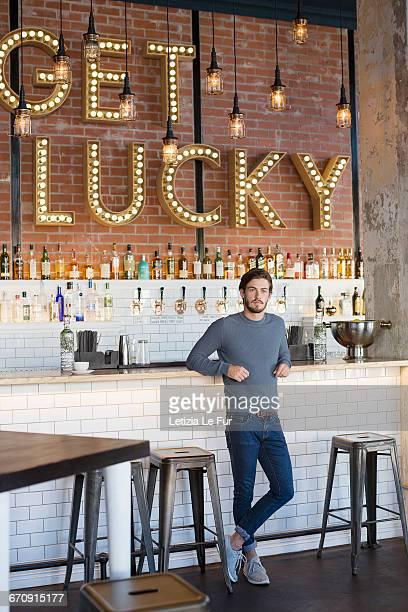 Young man standing at bar counter