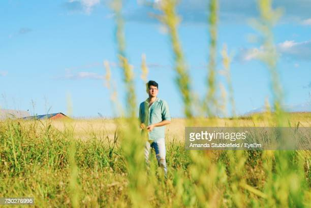 Young Man Standing At Farm Against Blue Sky
