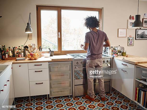 Young man standing at stove in kitchen