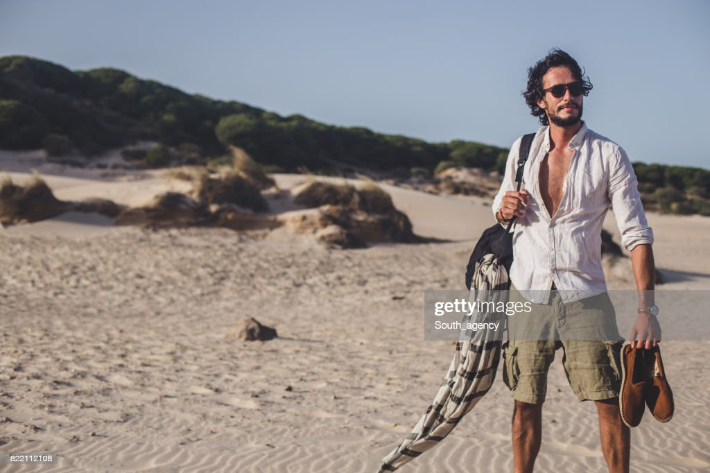Young man standing at the beach : Stock Photo