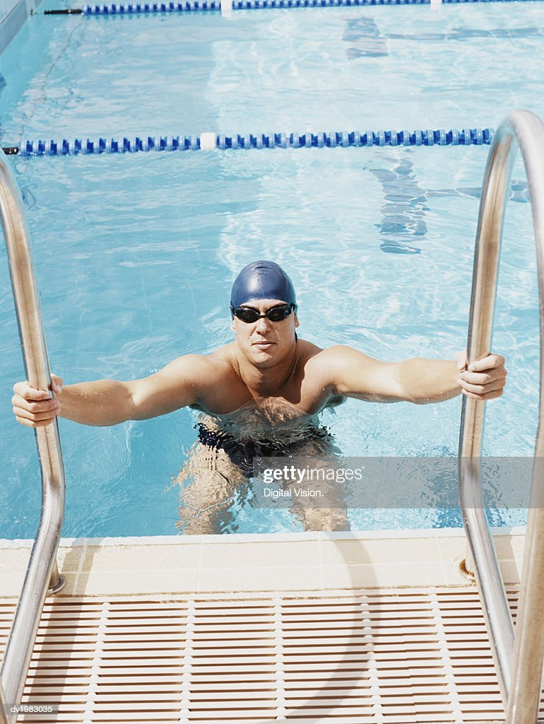 Young Man Standing at the Edge of a Swimming Pool : Stock Photo