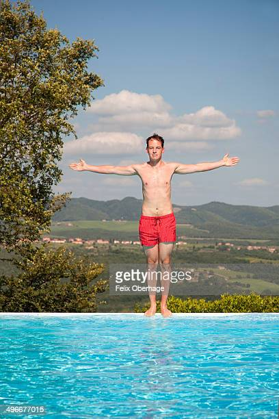 young man standing at the pool with arms wide open