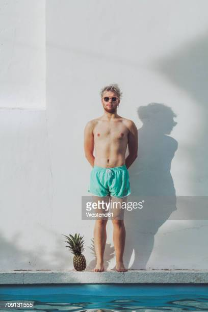 young man standing at the poolside next to pineapple - badkleding stockfoto's en -beelden