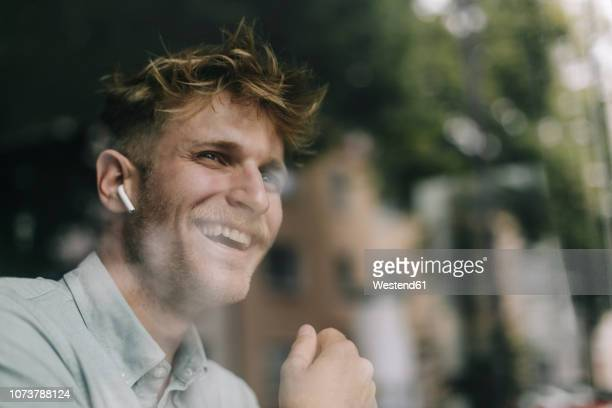 young man standing at the window, using ear buds, laughing - drahtlose technologie stock-fotos und bilder