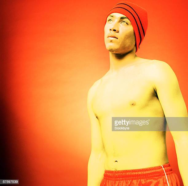 young man standing bare-chested wearing cap (infrared) - barechested bare chested ストックフォトと画像