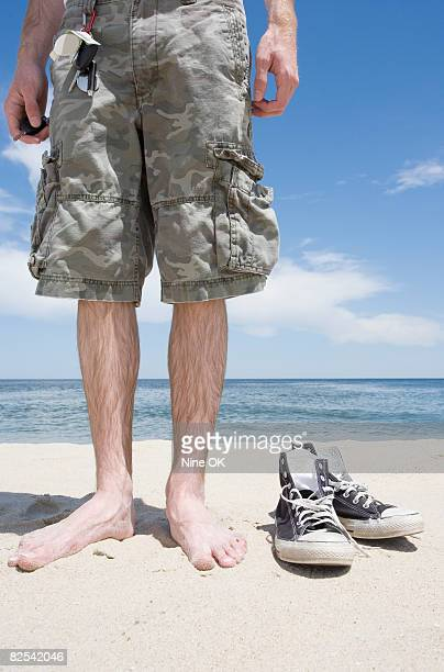 young man standing barefoot on beach - poilu photos et images de collection