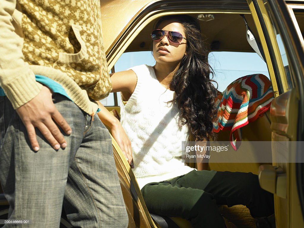 Young Man Standing Beside Car, Young Woman Sitting In Back Seat : Stock  Photo