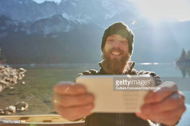 Young man standing beside lake, taking selfie, using smartphone, Garmisch-Partenkirchen, Bavaria, Germany