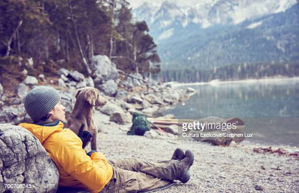 Young man standing beside lake, taking selfie, using smartphone, Garmisch-Partenkirchen, Bavaria, Germany