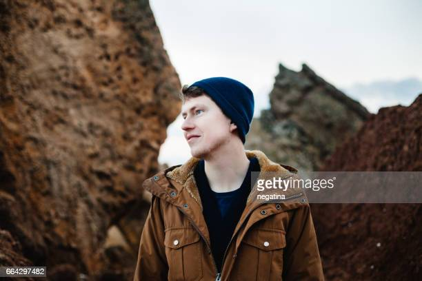 young man standing between brown rocks looking left - brown jacket stock pictures, royalty-free photos & images