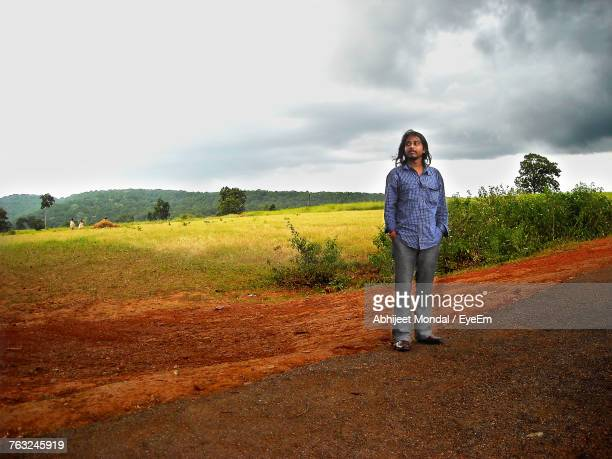 Young Man Standing By Agricultural Field Against Cloudy Sky