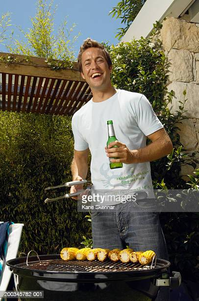 Young man standing by bbq cooking corn, laughing, portrait