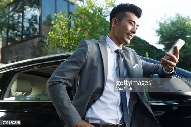 Young man standing by car and using cell phone
