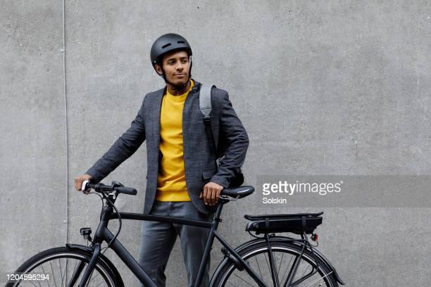 young man standing by electric bicycle - casque de protection au sport photos et images de collection