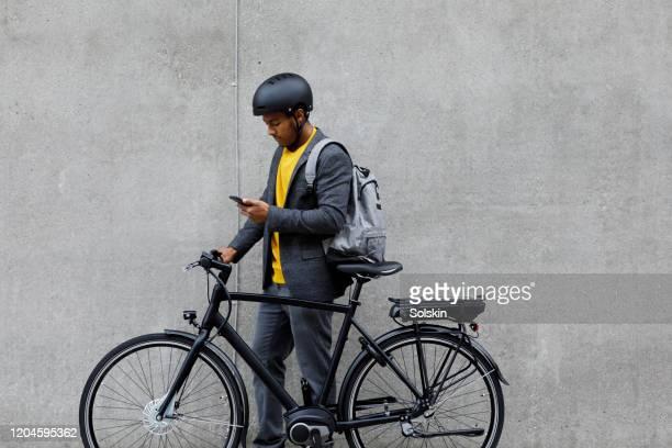 young man standing by electric bicycle using smartphone - a caminho - fotografias e filmes do acervo