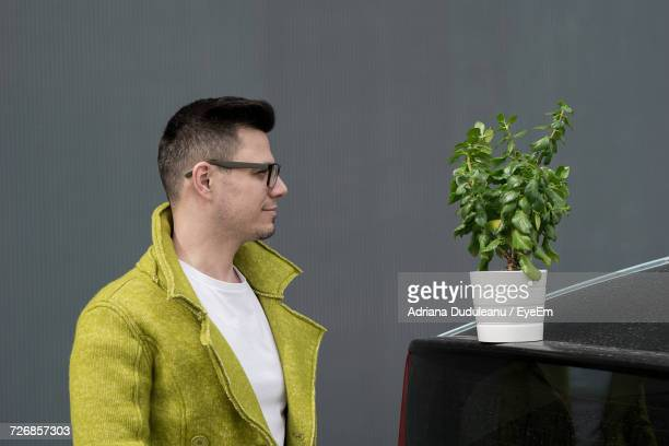 Young Man Standing By Houseplant Against Gray Wall