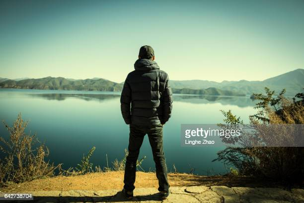 Young man standing by lake