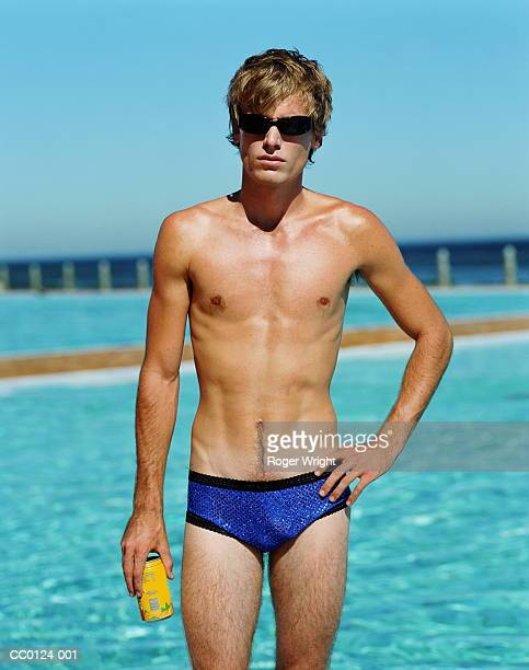 young man standing by swimming pool, holding can, portrait - young men in speedos stock pictures, royalty-free photos & images