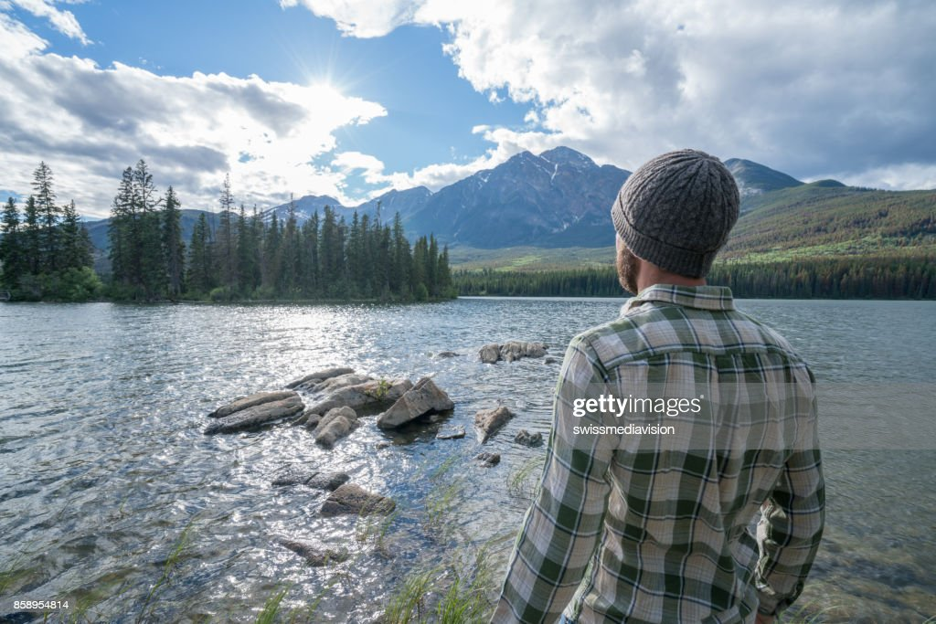 Young man standing by the lake looking at mountain scenery : Stock Photo