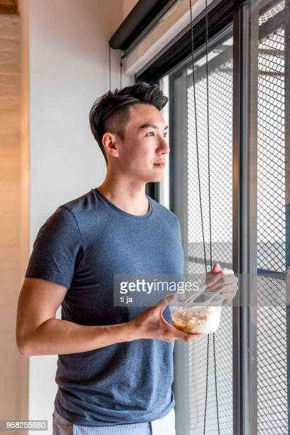 young man standing by the window with food - handsome chinese men stock pictures, royalty-free photos & images