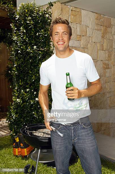 Young man standing holding beer bottle and bbq tongs, portrait