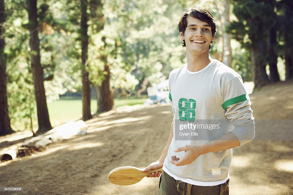 Young Man Standing in a Forest Holding a Wooden Racket : Stock Photo