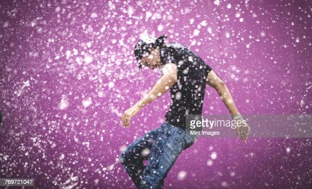 young man standing in a shower of water drops. - wet jeans stock photos and pictures